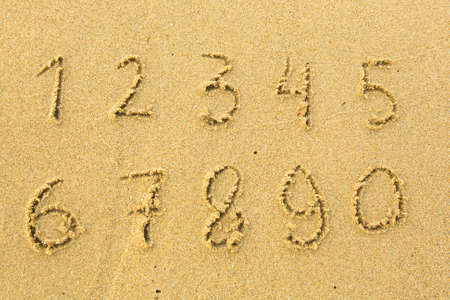 Numbers from one to ten written on a sandy beach. photo