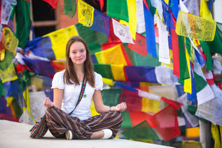 Teengirl sitting on Buddhist stupa, prayer flags flying in background. photo