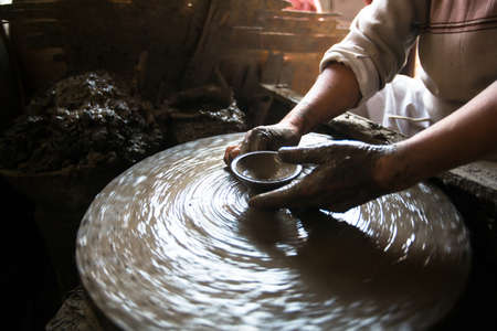 potters wheel: Close-up of hands working clay on potters wheel.