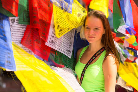 Young girl and Buddhist prayer flags flying in the Buddhist monastery. photo