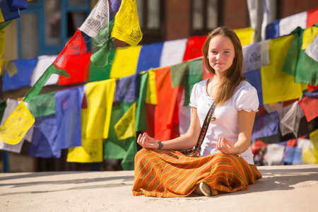 Girl sitting on Buddhist stupa, prayer flags flying in background. photo