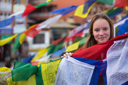 Young girl and Buddhist prayer flags flying.  photo