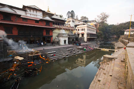 ghat: KATHMANDU, NEPAL - DEC 20: During the cremation ceremony along the holy Bagmati River in Bhasmeshvar Ghat at Pashupatinath temple, Dec 20, 2013 in Kathmandu, Nepal.
