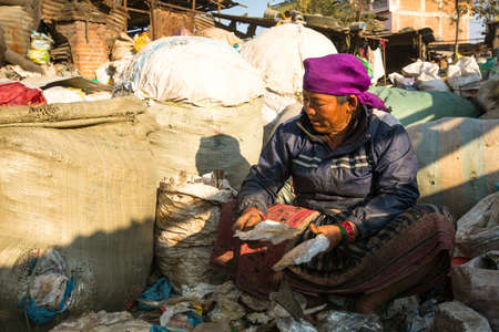 poorer: KATHMANDU, NEPAL - DEC 22, 2013: Unidentified woman from poorer areas working in sorting of plastic on the dump, Dec 22, 2013 in Kathmandu, Nepal. Only 35% of population have access to adequate sanitation.