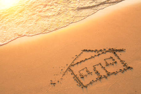 sand drawing: House painted on beach sand. Stock Photo