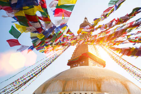 Bodhnath Stupa in Kathmandu with Buddha Eyes - shot against the sun. Stock Photo