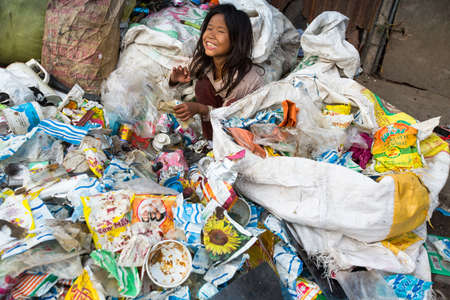 developing country: KATHMANDU, NEPAL - DEC 19: Unidentified child is sitting while her parents are working on dump, Dec 19, 2013 in Kathmandu, Nepal. In Nepal annually die 50,000 children, in 60% of cases -malnutrition.