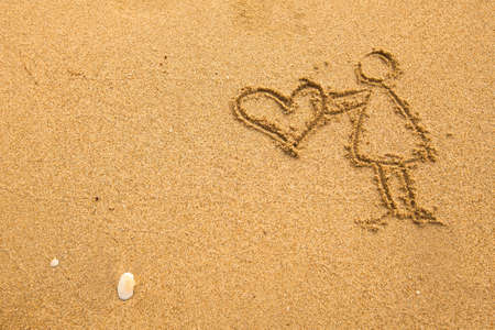 In texture of sand: girl holding a big heart. Stock Photo