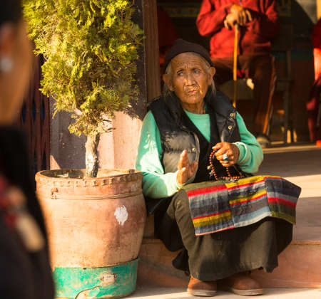 stupa one: KATHMANDU, NEPAL - DEC 11, 2013: Portrait of unidentified old woman near stupa Boudhanath. Stupa is one of the largest in the world, of 1979 is a UNESCO World Heritage Site.