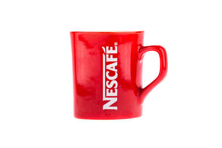 branded: KRAKOW, POLAND - FEB 3, 2014: Studio shot of a branded mug Nescafe coffee. Nescafe is a brand of Swiss food and beverage company Nestle SA - is largest food company in the world measured by revenues.