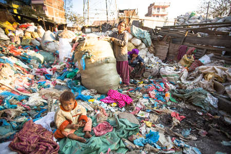 annually: KATHMANDU, NEPAL - DEC 22, 2013: Unidentified child is sitting while her parents are working on dump. In Nepal annually die 50,000 children, in 60% of cases - malnutrition. Editorial