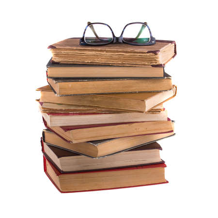 quantity: Stack of old books and spectacles in thick-rimmed, isolated on white background.