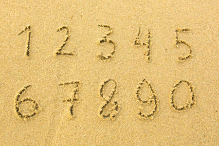 Numbers one to ten written on a sandy beach. photo