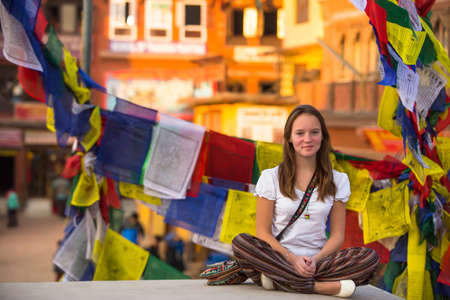 Girl sitting in the Lotus position on Buddhist stupa, prayer flags flying in the background. photo