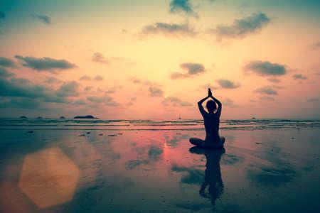 Silhouette junge Frau praktizieren Yoga am Strand bei Sonnenuntergang. Standard-Bild