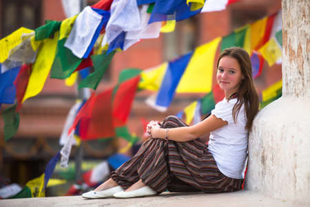 Young girl sitting on Buddhist stupa, prayer flags flying in the background. photo