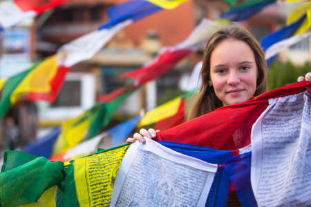 Teengirl and Buddhist prayer flags. photo