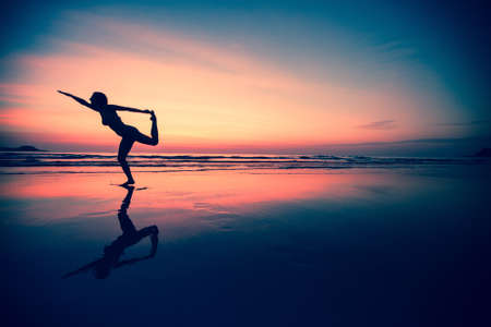 Silhouette of a woman practicing yoga on the beach at sunset. photo