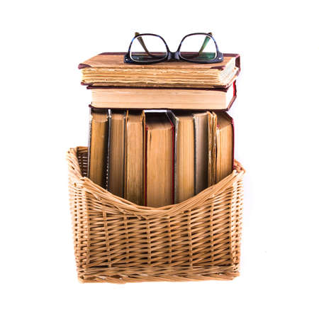 Stack of old antique books in a wicker basket and spectacles lying on top, isolated on white background. photo