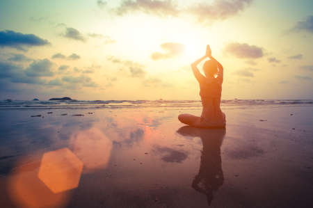 Silhouette young woman practicing yoga on the beach at surrealistic sunset. Stock Photo