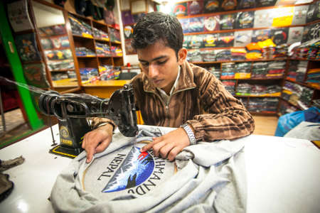 KATHMANDU, NEPAL - DEC 20, 2013: Unidentified Nepali man does embroidery on clothes in a small workshop. Nepal is one of the poorest and least developed countries of the world, unemployment rate of 46 %. Editorial