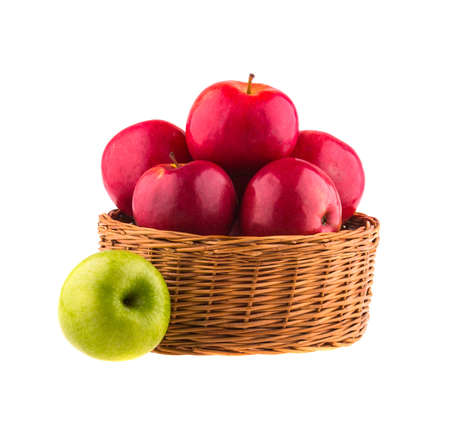 Fresh red and one green apples in a wooden basket, isolated on white background. photo