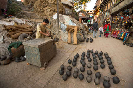 BHAKTAPUR, NEPAL - DEC 7, 2013: Unidentified Nepalese man working in the his pottery workshop. More 100 cultural groups have created an image Bhaktapur as Capital of Nepal Arts. Editorial