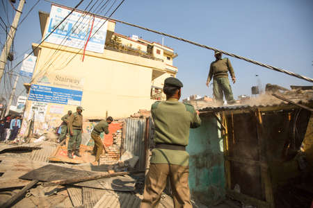 KATHMANDU, NEPAL - DEC 24, 2013: Unknown nepalese police during a operation on demolition of residential slums. In KTM is home to 50,000 squatters spread across city slums. Editorial