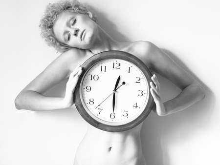 scrawny: Scrawny blond girl with big clock in hands, black and white photo. Stock Photo