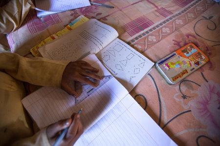 KATHMANDU, NEPAL - DEC 9, 2013: Unknown children doing homework at Jagadguru School. School established at 2013, to let new generation learn Sanskrit and preserve Hindu culture. Stock Photo - 26842342