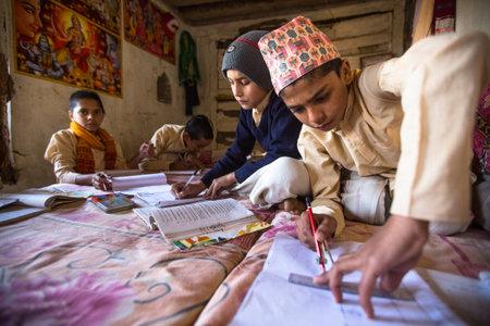 KATHMANDU, NEPAL - DEC 9, 2013: Unknown children doing homework at Jagadguru School. School established at 2013, to let new generation learn Sanskrit and preserve Hindu culture. Stock Photo - 26842382