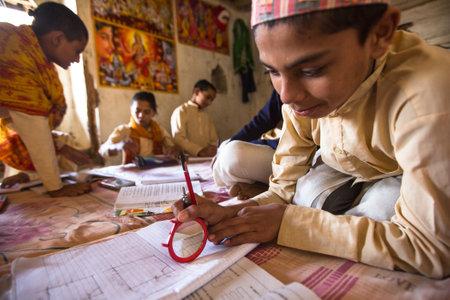 KATHMANDU, NEPAL - DEC 9, 2013: Unknown children doing homework at Jagadguru School. School established at 2013, to let new generation learn Sanskrit and preserve Hindu culture. Stock Photo - 26842383