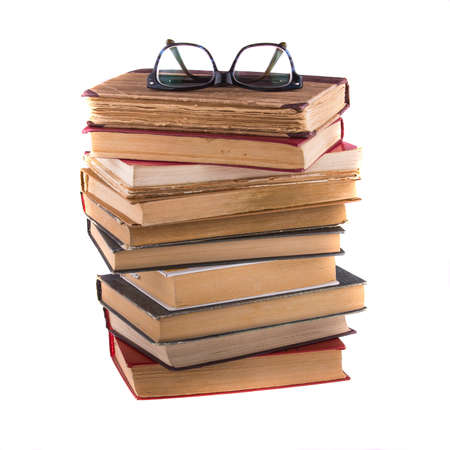 rimmed: Stack of old antique books and spectacles in thick-rimmed, isolated on white background.