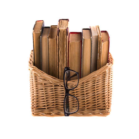 rimmed: Stack of old antique books in a wicker basket and spectacles in thick-rimmed, isolated on white background.