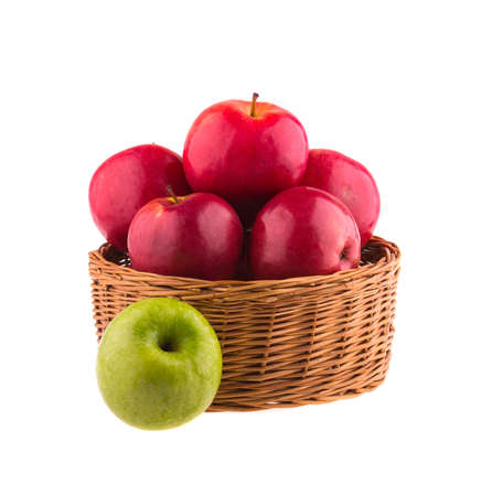 Red and one green apples in a wooden basket, isolated on white background. photo