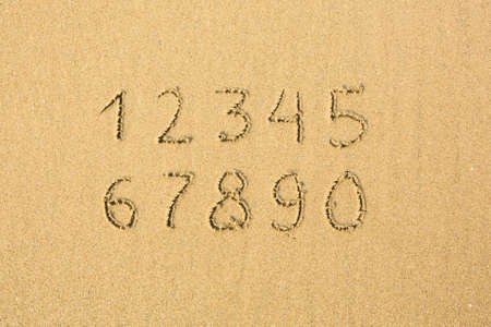 Numbers written on a sandy beach. photo
