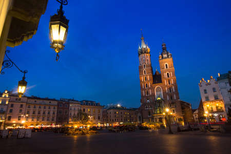 KRAKOW, POLAND - APR 7, 2014: St. Marys Church on Rynek Glowny (Market Square) in night time. Rynek Glowny - roughly 40,000 m2 is largest medieval town square in Europe.