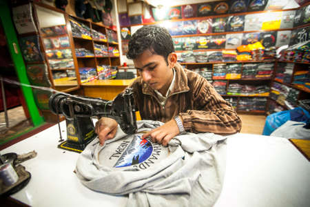 unemployment rate: KATHMANDU, NEPAL - DEC 20, 2013: Unidentified Nepali man does embroidery on clothes in a small workshop. Nepal is one of the poorest and least developed countries of the world, unemployment rate of 46 %. Editorial