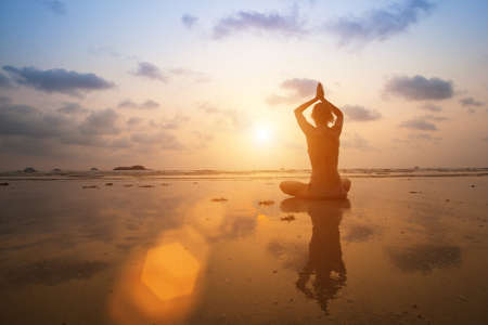 Silhouette young woman practicing yoga on the beach at sunset. Stock Photo - 27363017