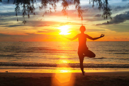 Silhouette young woman practicing yoga on the beach at sunset. Stock Photo - 27363023