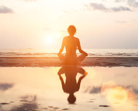 Yoga woman sitting in lotus pose on the beach during sunset, with reflection in water. Stock Photo - 27363025
