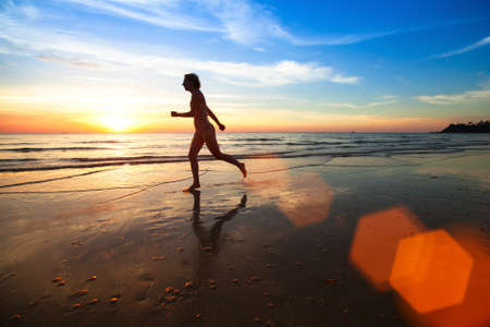 Silhouette of a young woman jogger at sunset on the seashore. Stock Photo - 27363068