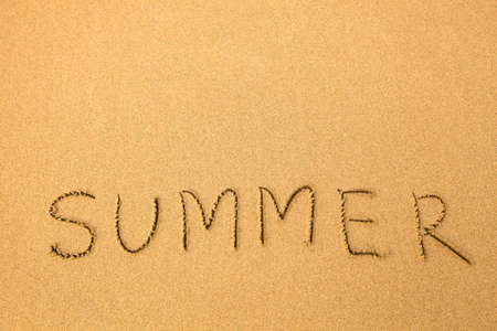 Summer - text written by hand in sand on a beach. photo