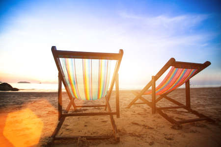 loungers: Perfect vacation concept, pair of beach loungers on the deserted coast sea at sunrise. Stock Photo