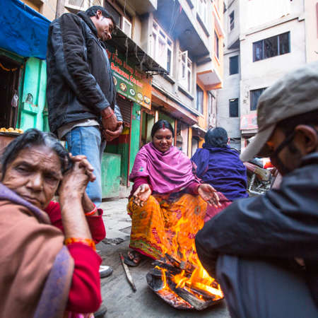 KATHMANDU, NEPAL - DEC 25, 2013: Unidentified poor people warm themselves by the fire in the street at slums. Caste of untouchables in Nepal, is about 7 % of population.