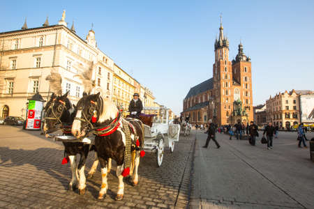 KRAKOW, POLAND - FEB 26, 2014: Carriages at Main Market Square. It dates to the 13th century, and at roughly 40,000 m it is the largest medieval town square in Europe.