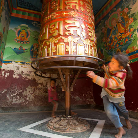 the stupa: KATHMANDU, NEPAL - DEC 23, 2013: Unidentified children have fun with spinning Big Tibetan Buddhist prayer wheel at Boudhanath Stupa. Editorial
