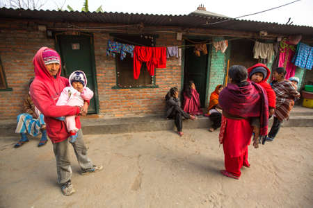 KATHMANDU, NEPAL - DEC 19, 2013: Unidentified local people near their homes in a poor area of the city. The caste system is still intact today but the rules are not as rigid as they were in the past.