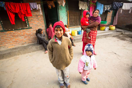 KATHMANDU, NEPAL - DEC 19, 2013: Unidentified local children near their homes in a poor area of the city. The caste system is still intact today but the rules are not as rigid as they were in the past.