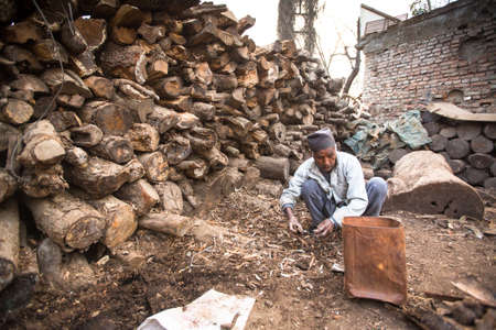 rites: KATHMANDU, NEPAL - DEC 19, 2013: Unidentified a man sort wood for cremation rites in Bhasmeshvar Ghat at Pashupatinath temple in Kathmandu.  Editorial